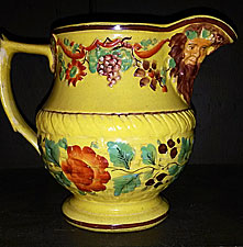 SOLD Yellow-glazed jug with masks