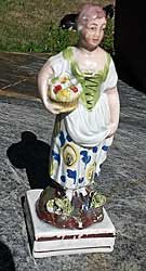 Figure of girl with basket of fruit